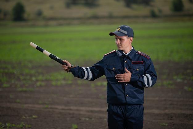 Полицейский в форме с жезлом в руке на фоне сельского пейзажа