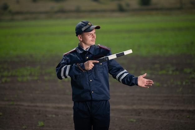 Полицейский в форме с жезлом в руке