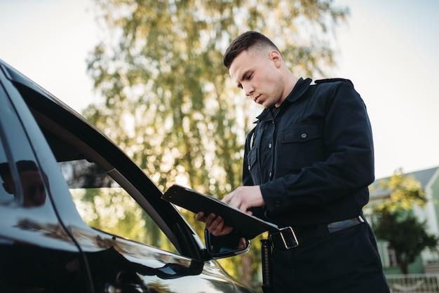 제복을 입은 경찰관이 여성 운전자에게 벌금을 씁니다.