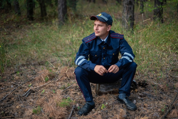 Policeman sits on the grass in the forest and thinks