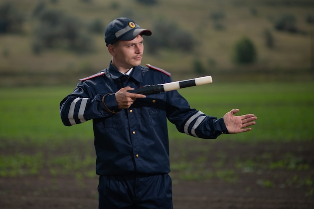 Policeman in uniform with a rod in his hand on the background of rural landscape