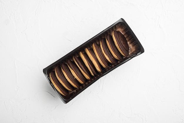 디저트용 폴란드어 초콜릿 칩 쿠키, 플라스틱 트레이 용기, 플라스틱 트레이 용기, 흰색 석재 테이블 배경, 상단 뷰 플랫 레이, 텍스트 복사 공간