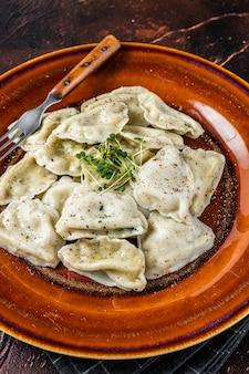 허브와 버터를 곁들인 접시에 감자를 곁들인 폴란드 피에로기 만두. 어두운 배경입니다. 평면도.