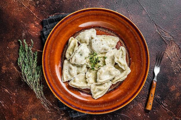 허브와 버터를 곁들인 접시에 감자를 넣은 폴란드 피에로 기 만두. 평면도.