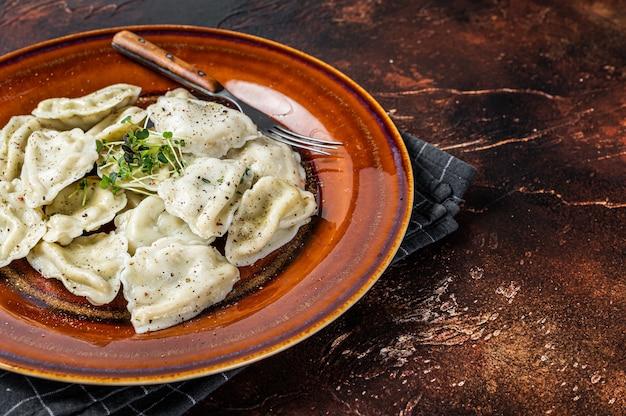 허브와 버터를 곁들인 접시에 감자를 곁들인 폴란드 피에로기 만두