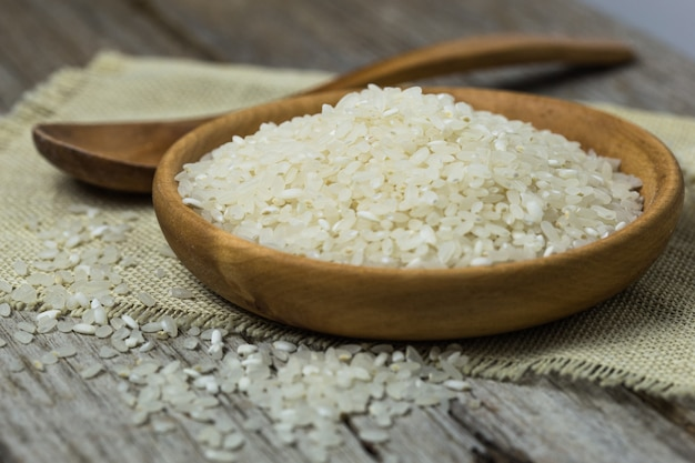 Polished white rice in wooden spoon. long grain rice and round grain rice background. rice pattern rice basmati rice photo raw rice polished rice dry rice.