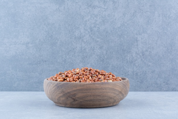 Polished wooden bowl stocked with red beans on marble surface