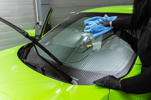 Polishing the car glass with a blue microfiber cloth.