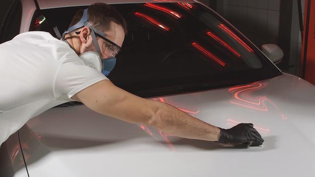 Полируя машину керамикой, мужчина полирует машину воском