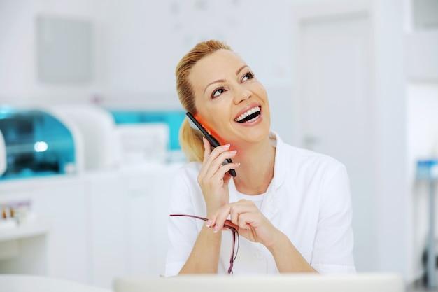 예의 바른 매력적인 금발 웃는 실험실 조교가 실험실에 앉아 환자에게 좋은 소식을 전합니다.