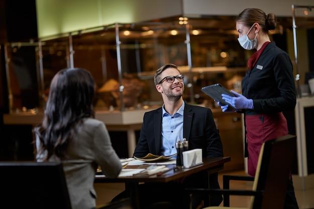礼儀正しいビジネスマンは注文についてウェイトレスに取り組んでいます