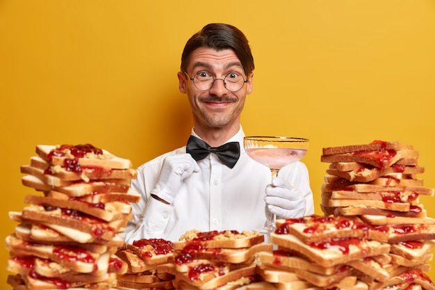 Polite cheerful waiter wears uniform, holds glass , presents new alcoholic beverage for restaurant visitors, has hairstyle and mustache, stands near pile of delicious sandwiches indoor