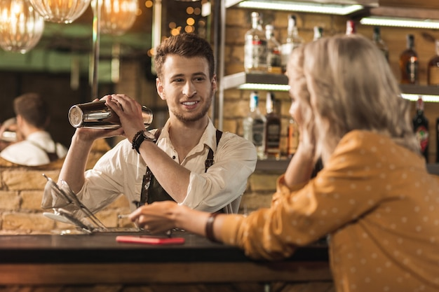 Polite conversation. pleasant young barman making a cocktail and smiling at his customer while she talking to him