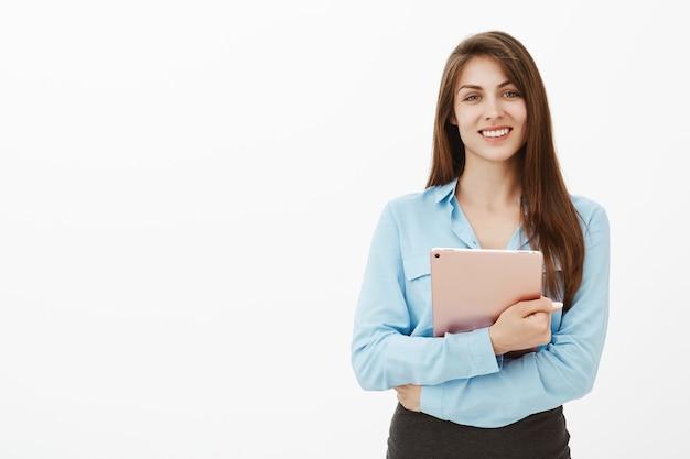 Donna di affari castana educata e amichevole che posa nello studio