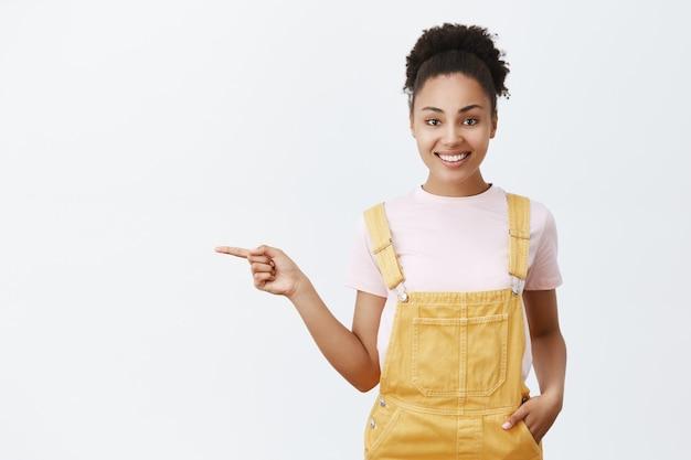 Вежливая, дружелюбная стильная афроамериканка в желтом комбинезоне, указывая влево и широко улыбаясь, указывая дорогу