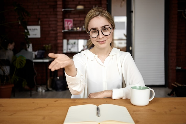 Polite human resources manager in eyewear sitting at her desk extending hand at camera, open to cooperation, making welcoming sign, saying: please take seat. friendly businesswoman greeting partner