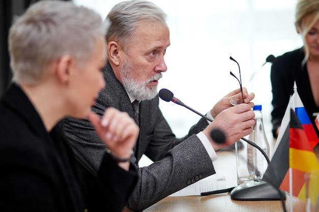 Политический саммит представителей разных стран и обсуждение международных вопросов, встречи без галстуков. в современном светлом зале заседаний