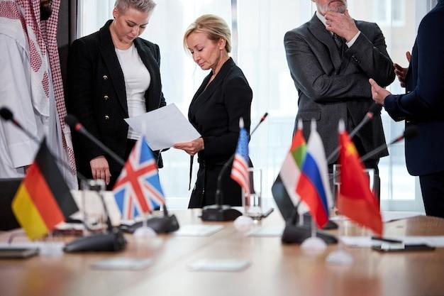 さまざまな国の代表者の政治サミットと国際的な質問の議論、関係のない会議。モダンな明るい会議室で