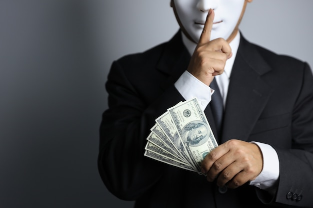 Politician or businessman wearing black suit and white mask show banknotes