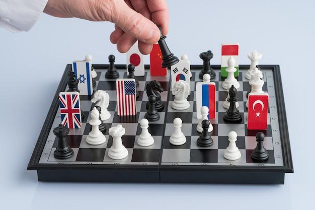 정치인의 손이 체스 말을 움직입니다. 정치 게임 및 전략의 개념적 사진입니다.
