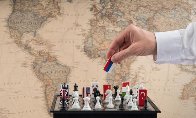 정치인의 손은 깃발이 달린 체스 조각을 움직입니다. 정치 게임의 개념적 사진