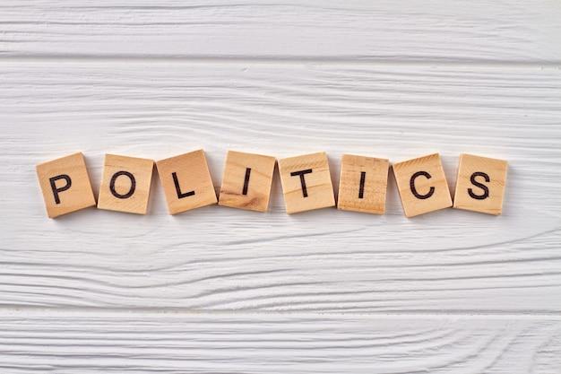政治と政府の概念。木の板に分離された木製の立方体の文字。