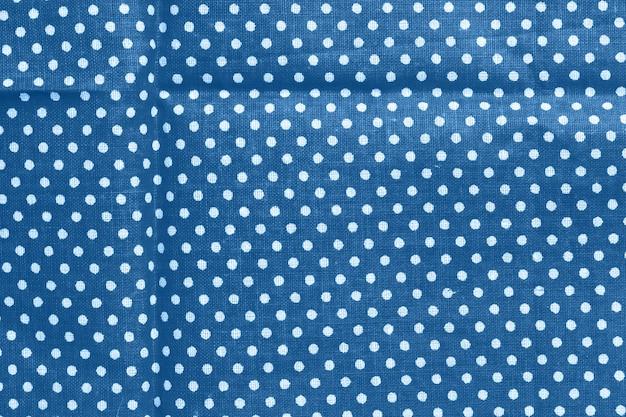 Горошек на синем фоне текстуры хлопка холста
