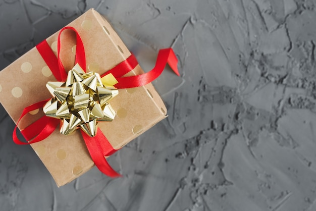 Подарочная коробка из бумаги в горошек с красной лентой и золотым бантом на бетонном фоне