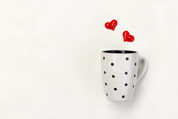 コピースペースと白い背景の上の赤いハートと水玉の白いカップ。バレンタインデーのコンセプト。
