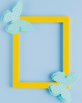 Polka dotted butterfly on yellow border frame over blue background