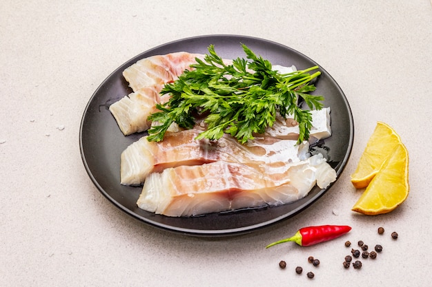 生のスケトウダラ(pollachius virens)ピース。健康的な食生活のための新鮮な魚。レモン、パセリ、海塩、唐辛子、黒胡pepper