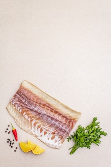 Филе сырого минтая (pollachius virens). свежая рыба для здорового образа жизни. лимон, петрушка, морская соль, перец чили, черный перец