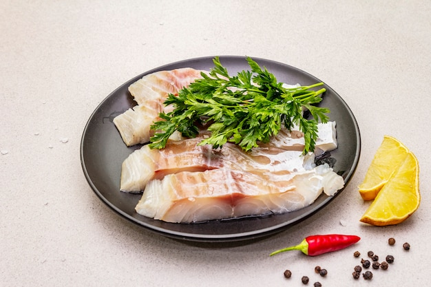 Сырой минтай (pollachius virens) шт. свежая рыба для здорового образа жизни. лимон, петрушка, морская соль, перец чили, черный перец