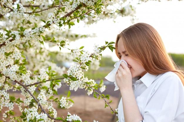 Симптом аллергии на пыльцу. боковой снимок молодой европейской самки чихает в носовой платок или дует в салфетке