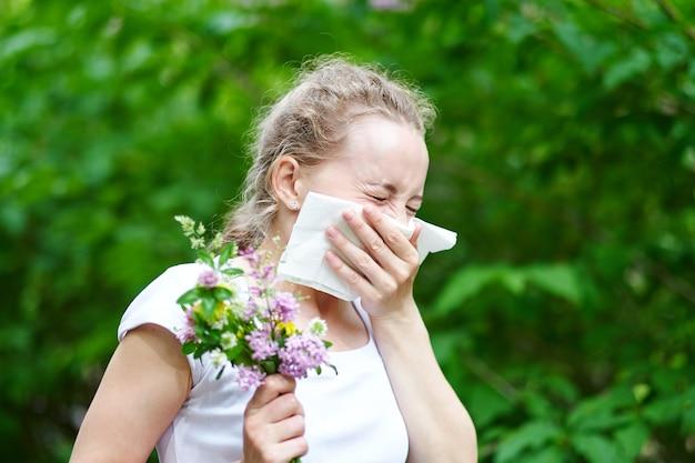 Аллергия на пыльцу, чихание женщины с букетом цветов. понятие: сезонная аллергия.