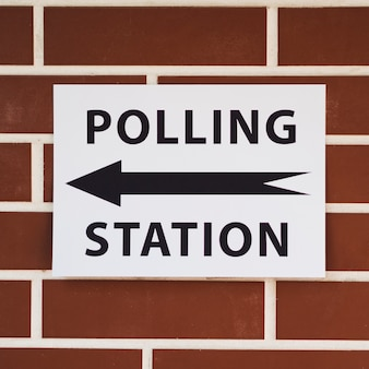 Polling station sign with direction on brick wall close-up