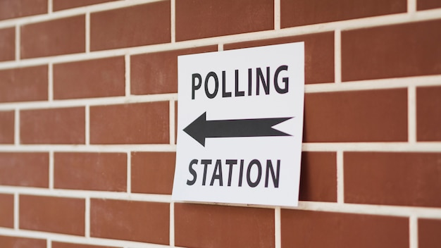 Polling station sign with direction on brick wall