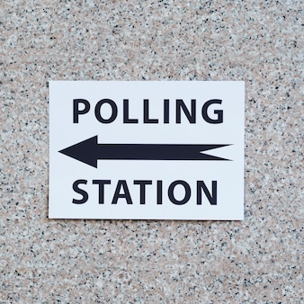 Polling station sign with direction on wall close-up