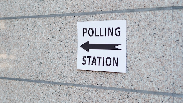 Polling station sign with direction on wall
