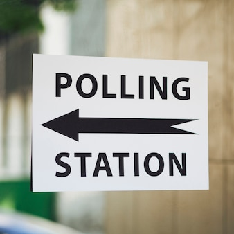 Polling station sign with direction on window close-up