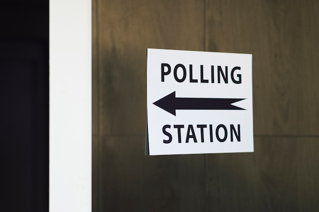 Polling station sign with direction on wooden wall
