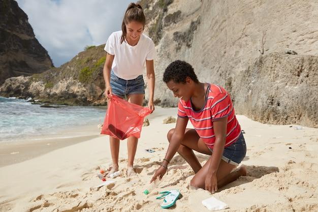 Загрязненный пляж с прекрасным пейзажем. две женщины смешанной расы собирают мусор в мешок для мусора