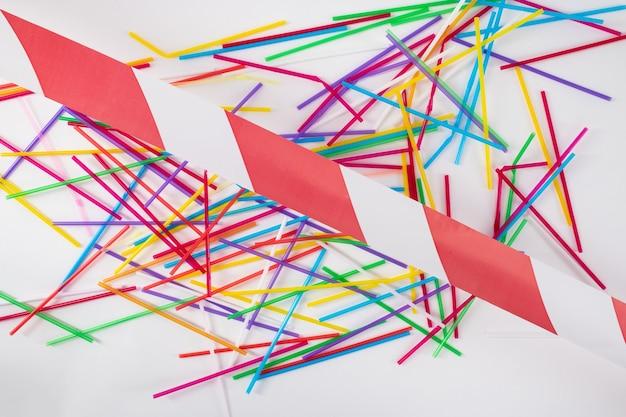 汚染されたライブ。床に横たわって赤と白の線で交差したカラフルな明るいストローの束