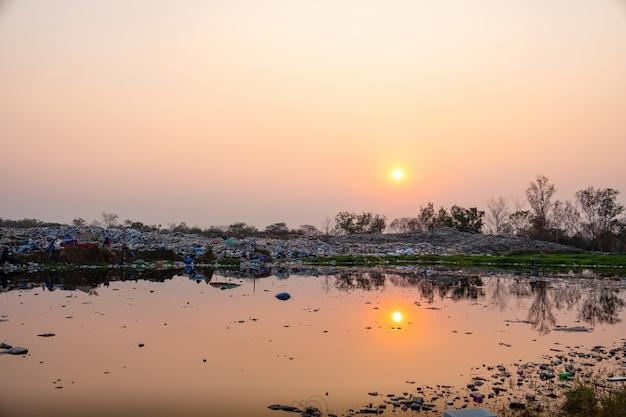 Загрязненная вода и горная куча мусора и загрязнение на солнце садится на заднем плане
