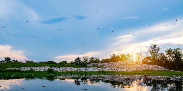 Загрязненная вода и гора большая куча мусора и загрязнение, куча вони и токсичных остатков