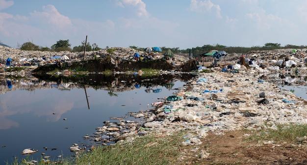 Загрязненная вода и горы большая куча мусора и загрязнение куча вони и токсичных остатков