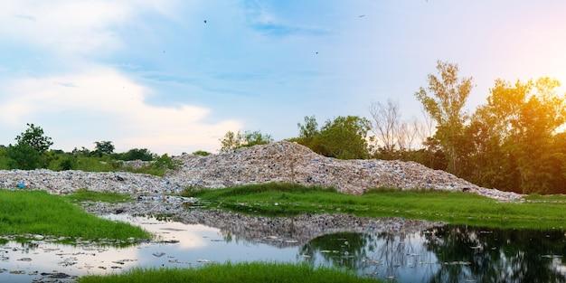 Загрязненная вода и горы, большая куча мусора, и загрязнение из-за городских