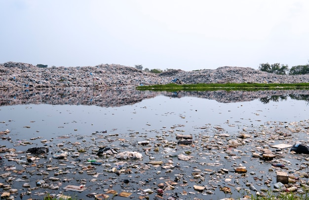 Polluted water and large mountain of garbage