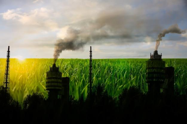 자연의 오염. 스모그가 있는 공장. 공기 중 위험한 연기. 배경에 녹색 잔디입니다.
