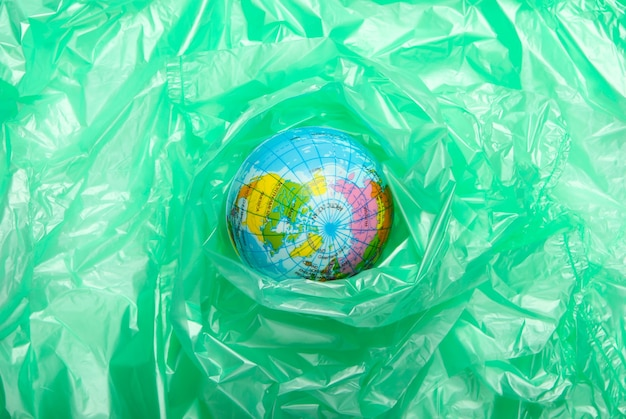 Pollution .plastic free. eco concept. globe wrapped in a plastic bag. save the planet. minimalism